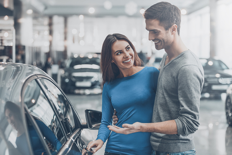Photo of a couple looking at a car in a showroom